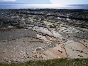 Sandstone pavement at low tide off the island of Mainland, Orkney. The Mouth of Hoy and part o fthe mountainous island of Hoy in the background
