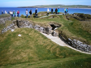 Skara Brae is situated next to Skaille Bay. When the village was built the sea would have been along the line of the mouth of the Bay. A great storm in 1859 blew away the layer of sand that had been covering the top of the village. The on-lookers are walking along the top of a sea wall that has been built to protect the site from coastal erosion.