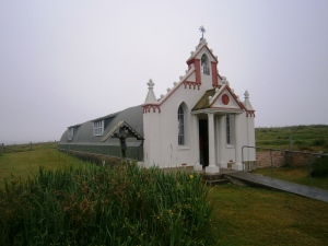 The Chapel exterior. The wayside shrine to the left is centred on a gift made in 1961 of Christ crucified  from Domenica Chiocchetti's home town of Moena to the people of Orkney with the cross and canopy made in Kirkwall.